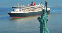 QM2 passing The Statue of Liberty