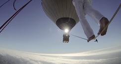 man walking between hot air balloons