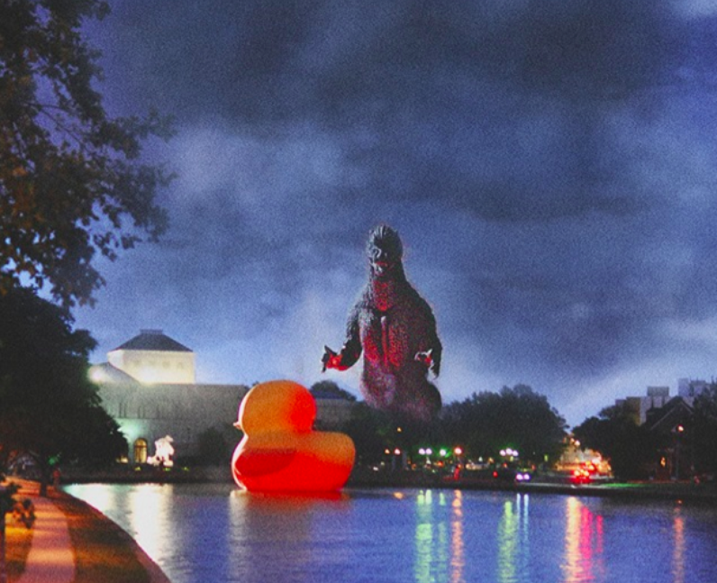 An inflatable duck and a Godzilla statue